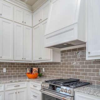 The contrast between the white cabinets and darker tiled backsplash adds coziness! And let's talk about the incredible crown molding along the ceiling! #shreveporthomes #designandbuild #kitchenbacksplash #crownmolding